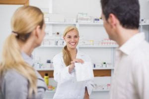 pharmacist giving a drug bag to patients in a parmacy