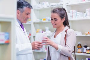 Pharmacist giving paper bag to his customer in the pharmacy